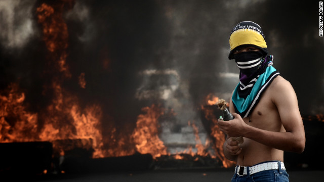 A Bahraini protester holds a molotov cocktail bomb next to a barricade on fire during clashes with riot police in a Shiite suburb of the capital Manama, on April 20, 2012 following a demonstration to demand a halt to the Formula One Grand Prix event.