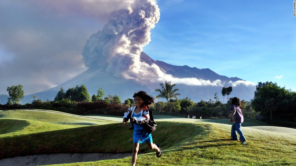 Indonesian girls play at a golf course in Sleman, near Yogyakarta, as a cloud of ash rises from Mount Merapi in the background. Indonesia raised its alert for the volcano to its highest level in October 2010 and ordered people living nearby to evacuate. It last erupted in June 2006, killing two people, but its deadliest activity occurred in 1930 when more than 1,300 people died.