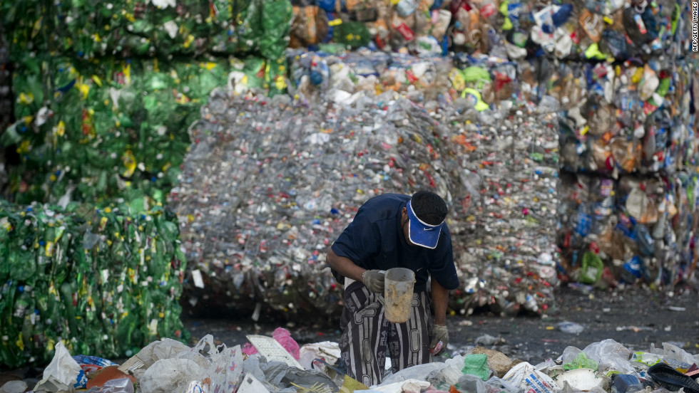 A scavenger classifies refuse in front of a pile of compacted bales of plastic bottles at the Bordo Poniente garbage dump in Mexico City. Some 6,000 tons of garbage from the second world's most populated city was deposited here daily for about 25 years until it was closed by the government in December 2011. The dump was considered one of the main sources of greenhouse gases in Mexico.