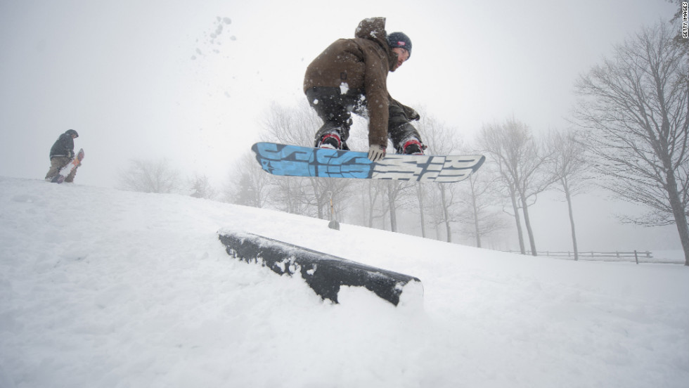 An employee of the Seven Springs Golf Resort snowboards off the seventh green in Somerset on Monday.