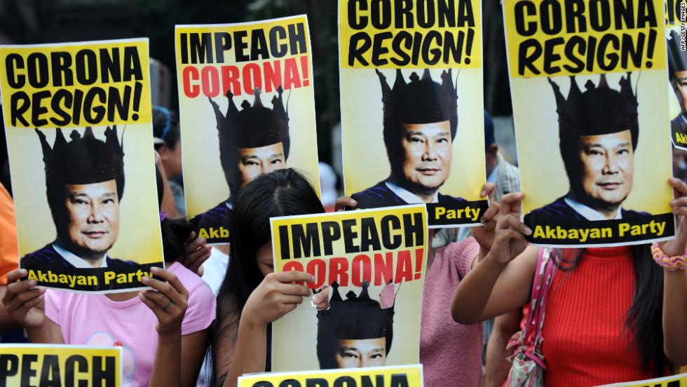Protesters hold placards with portraits of Philippine Supreme Court chief justice Renato Corona. The chief justice is being impeached in an ongoing and often televised trial.