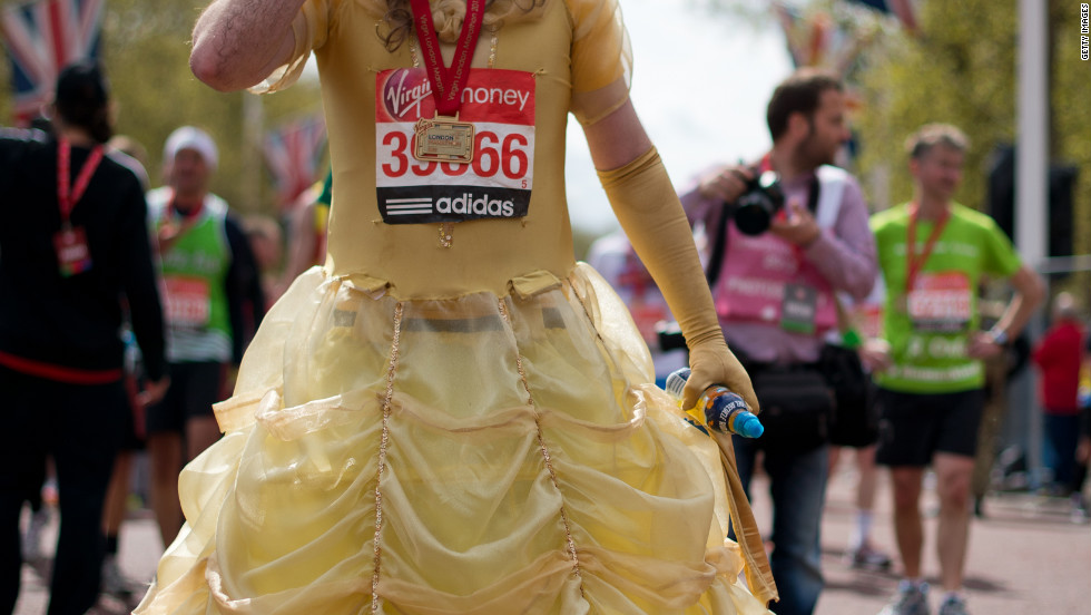A man in a dress catches his breath after crossing the line at the 2012 London Marathon. He was one of many runners to dress up at the event for charity.