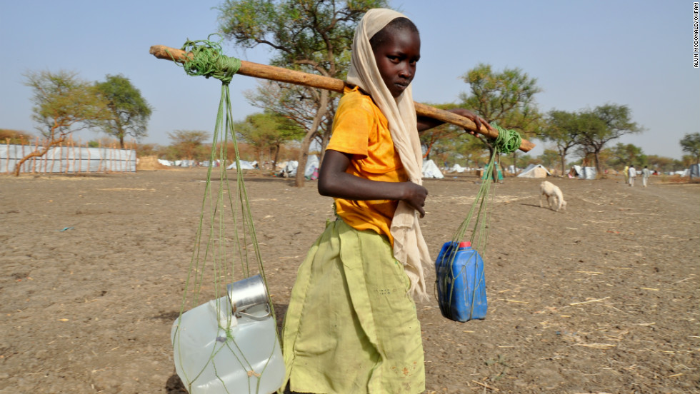 Women and girls wait in the hot sun for up to four hours, twice a day, to collect their families' water rations.
