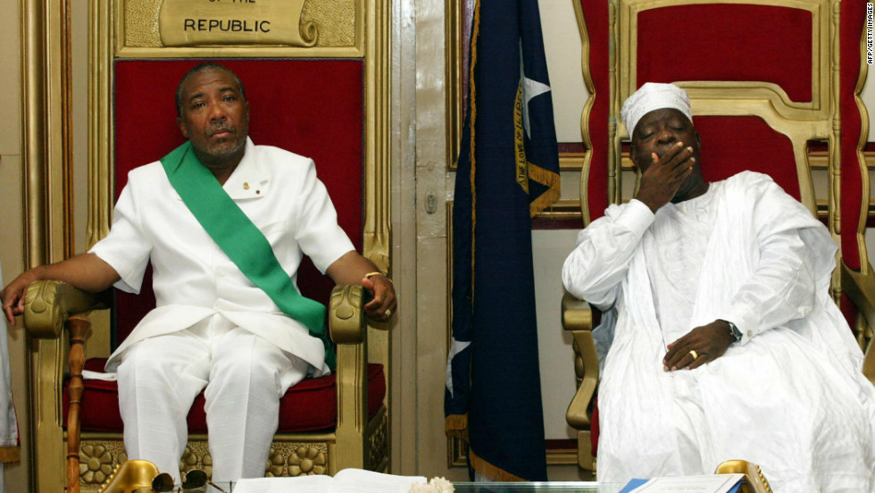 Charles Taylor, left, sits beside Liberia's new President Moses Zeh Blah during a swearing-in ceremony in Monrovia in August 2003.