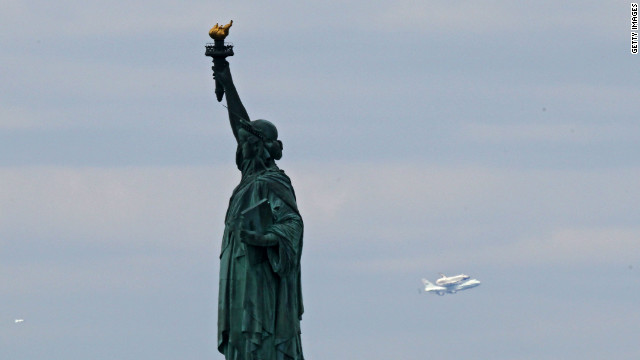 The space shuttle Enterprise passes the Statue of Liberty into New York City on the last leg of its final flight April 27, 2012.