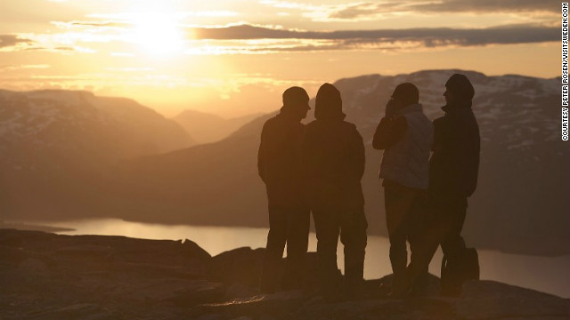A group look out to the midnight sun on top of Mount Nuolja