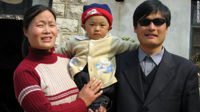 A picture dated March 28, 2005 shows blind activist Chen Guangcheng (R) with his wife and son Chen Kerui outside the home in Dondshigu village, northeast China's Shandong province. Chen, who gained worldwide fame for exposing abuses in China's 'one child' population policy, was freed on September 9, 2010, after four years in prison for accusing family-planning officials in eastern China's Shandong province of forcing at least 7,000 women to be sterilised or undergo late-term abortions. CHINA OUT AFP PHOTO (Photo credit should read STR/AFP/Getty Images)