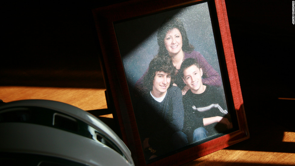 A photo of Janine, Ryan and his younger brother, Jacob, sits on the dining room table beside Ryan's lacrosse helmet.