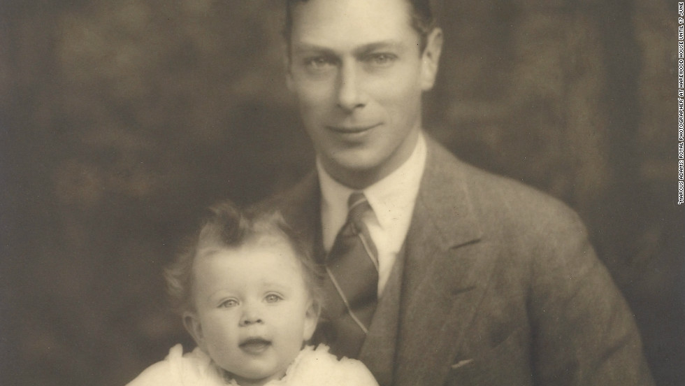 Prince Albert, later King George VI, proudly sits for a photograph with his young daughter and future monarch, Elizabeth.