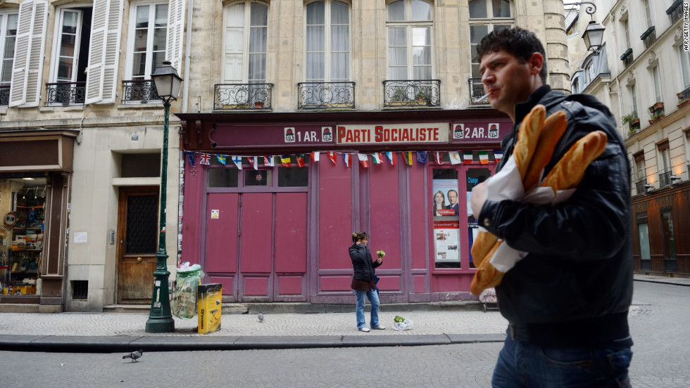 A man walks past a local office of the Socialist Party in Paris on Saturday, the day before the presidential runoff.