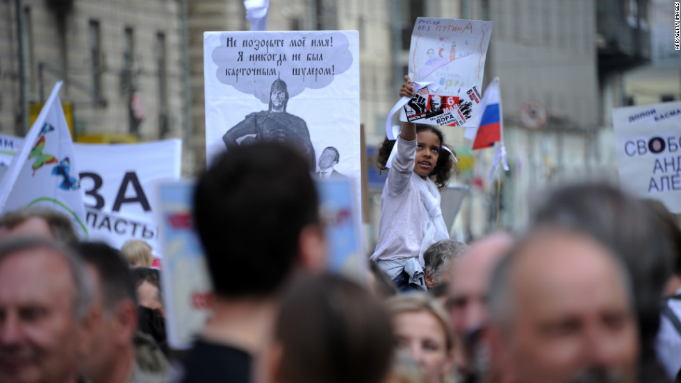 A young girl hoisted on someone's shoulders holds up a sign during the demonstration.