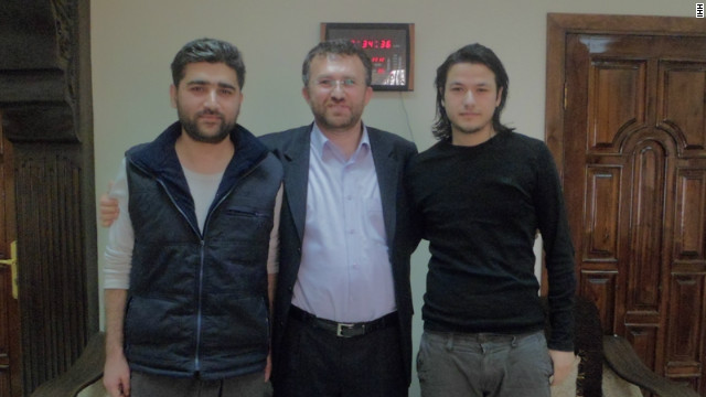 Reporters Adem Ozkose (L) and Hamit Coskun (R), appear with Bulent Yildiri (C) the leader of the Humanitarian Relief Foundation (IHH).