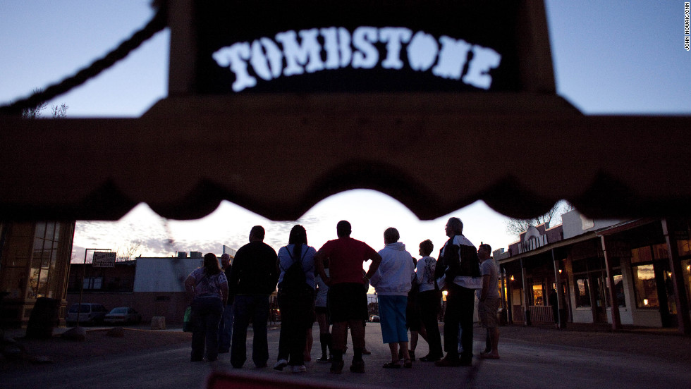 A tour group meets at sunset in downtown Tombstone, which receives as many as half a million visitors each year.