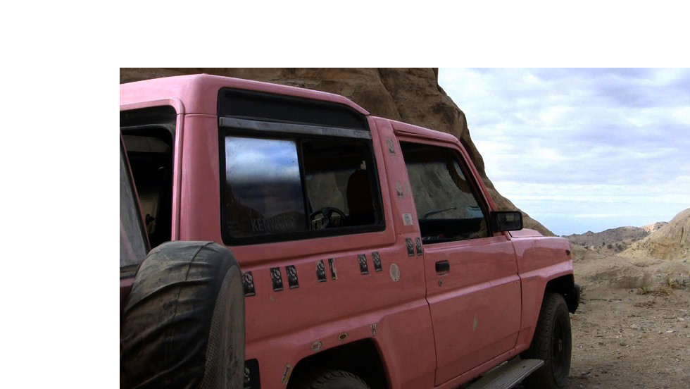 "Al-Bedoul's bright pink jeep, ""the couch surfing flag,"" is parked outside."