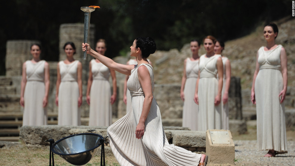 Amid the tumbledown columns and olive groves of the ancient stadium in Olympia, the high priestess holds the torch high at the lighting ceremony.