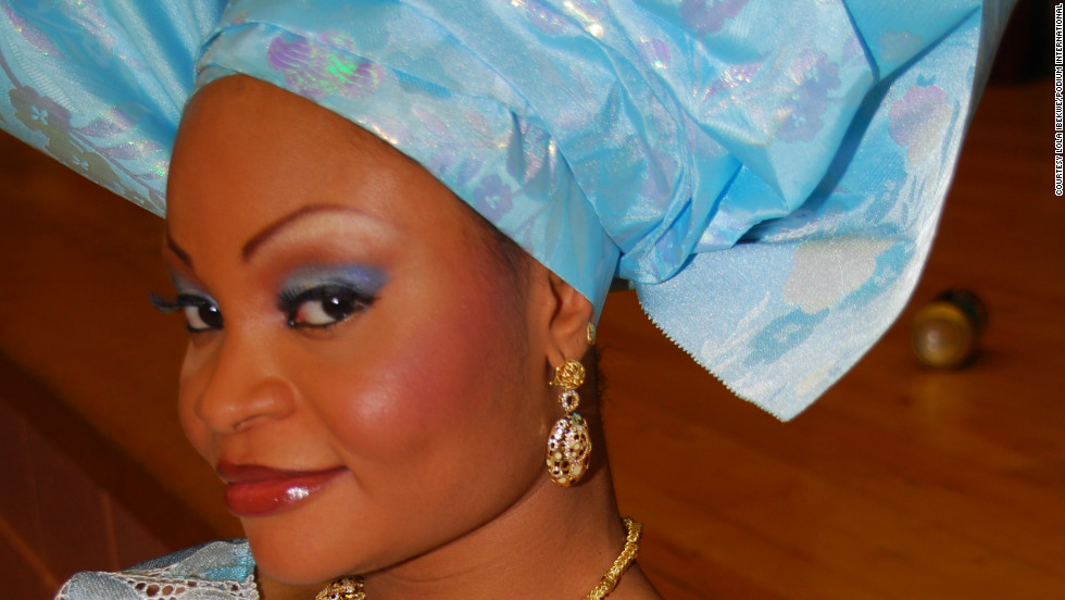 A bride wears a bright-hued outfit with embroidered detailing and traditional Nigerian gele headdress.