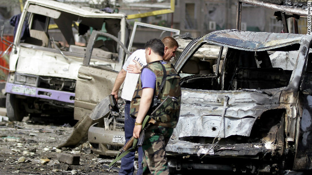 Syrian security forces inspect damage at the site of twin blasts in Damascus.