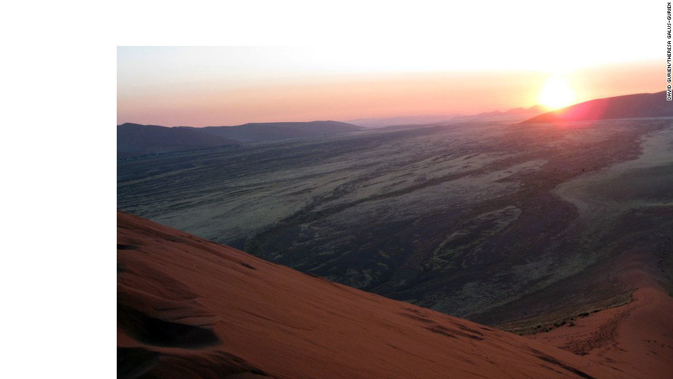 The sun rising over the dunes highlights the orange-red terrain.
