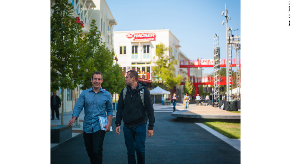 Facebook team members walk across the company's sprawling new campus on their way to Thursday night's Hackathon kickoff event.