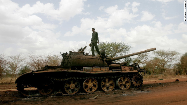 A Sudanese soldier stands atop a destroyed tank for Sudan People's Liberation Army of South Sudan in Heglig on April 23, 2012.