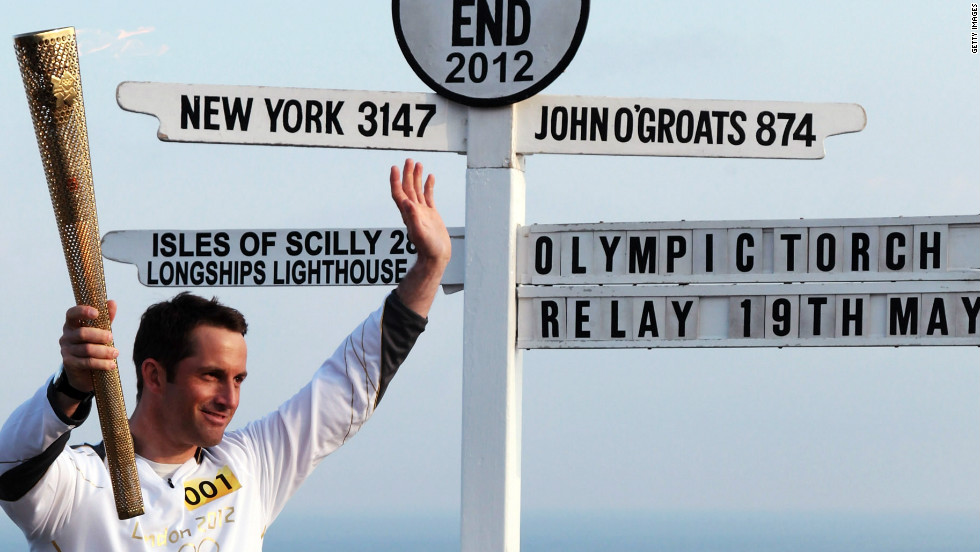 Olympic sailor and the first London 2012 torchbearer, Ben Ainslee, poses next to the Land's End sign in Cornwall.