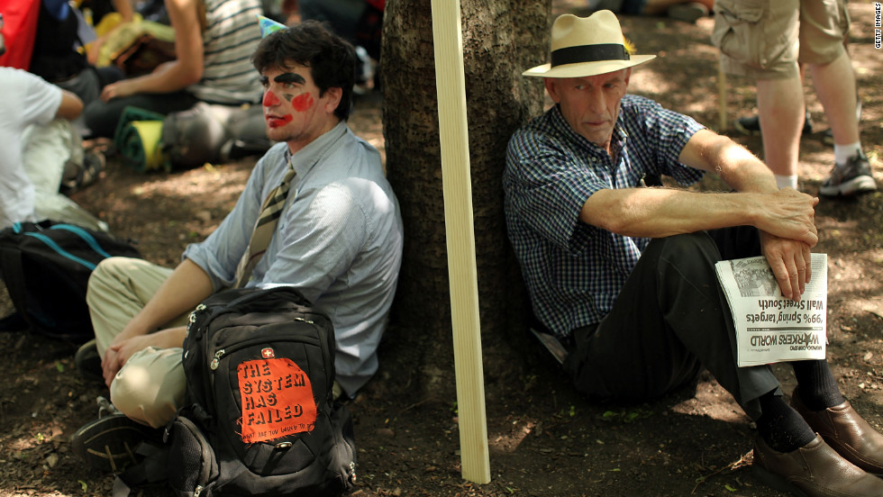 Two men rest against a tree before the start of protests on the first day of the NATO summit.
