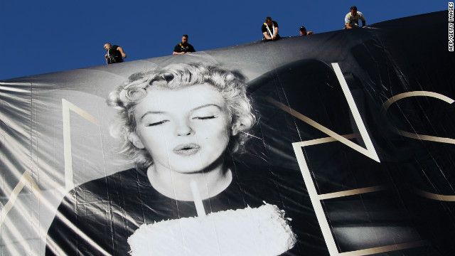 Workers set up a giant poster featuring Marilyn Monroe blowing out a birthday candle.