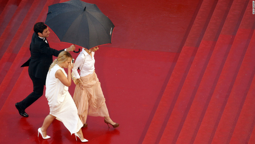 Guests arrive at Cannes during heavy rain on Sunday.