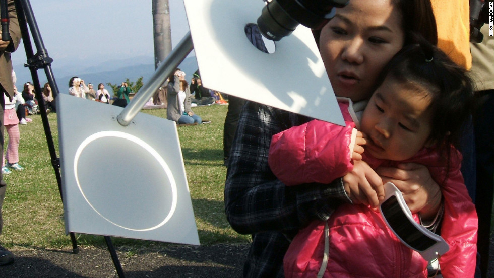 A girl and her mother observe the eclipse as it's projected onto a white background through a telescope in Tokyo.