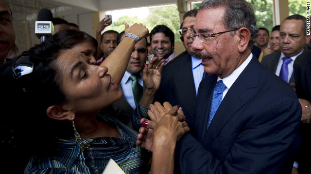 Danilo Medina, right, greets a supporter at a polling station in Santo Domingo on May 20, election day in the Dominican Republic.
