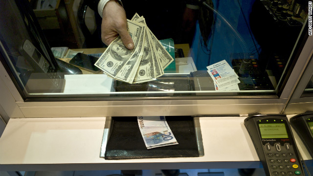 An employee of a currency exchange office displays US dollars next to a 20-euro note on January 6, 2012 in Lyon. The euro tumbled to yet another 16-month dollar low on Friday as the single currency's fortunes were hit by positive US jobs data and ongoing fears over the eurozone debt crisis. At 1400 GMT, the shared currency dived as low as $1.2725, which was last seen on September 13, 2010. It also sank to 98.21 yen, which was the lowest level since December 2000. AFP PHOTO / JEAN-PHILIPPE KSIAZEK (Photo credit should read JEAN-PHILIPPE KSIAZEK/AFP/Getty Images)