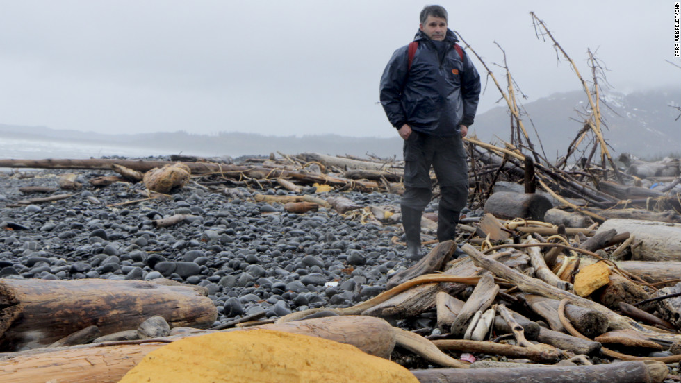 "Chris Pallister braves the elements on Montague Island to survey debris for the Marine Conservation Alliance.  He said the yellow urethane spray building foam insulation, which came from stockyards and from crushed structures in Japan, started showing up in January. ""We just never got much of that before, but if you walk up and down this beach you see big chunks,"" he said."