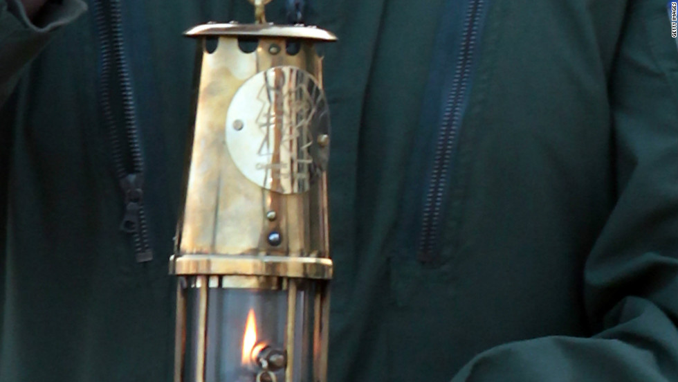Lieutenant Commander Richie Full delivers the Olympic flame at Land's End. Just two days later, on May 21, the torch went out as para-badmington star David  Follett carried it through Devon. It was relit using a back-up flame with Games chiefs admitting it was not uncommon for the torch to go out.