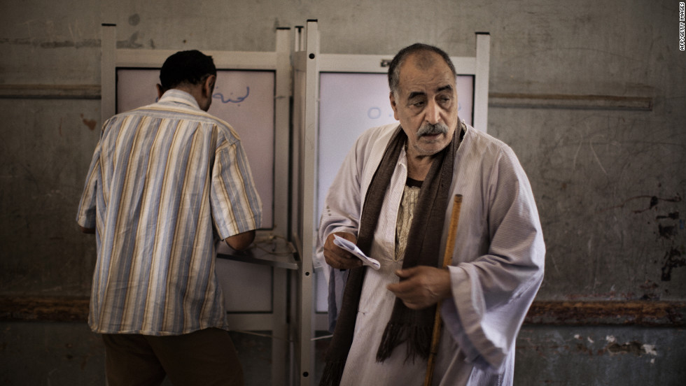 Egyptian men fill out their ballots at a Cairo polling place.