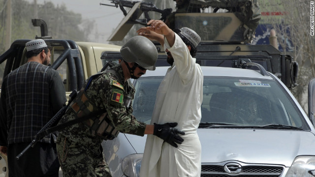 An Afghanistan National Army soldier searches a car's passenger in Kandahar, a largely Pashtun city.