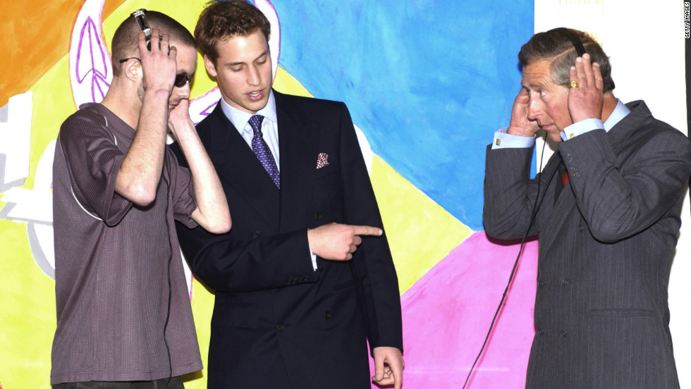 The Prince of Wales and his son Prince William talk with DJ Floyd during a visit to a day center for the homeless in Newport, Wales, on June 19, 2003.