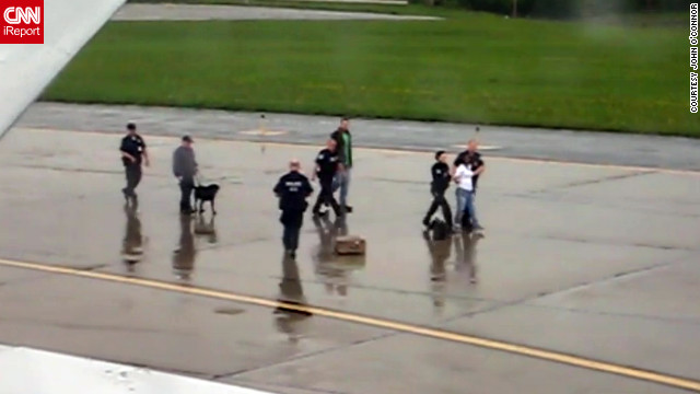 Lucie Zeeko Merigot is led away in handcuffs Tuesday while dogs sniff her luggage for explosives.