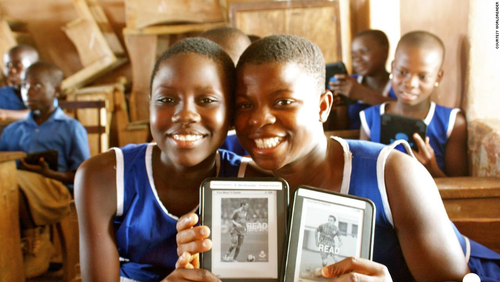 Two participants in the pilot project in Ghana hold up messages of encouragement from FC Barcelona stars Lionel Messi and Xavi. Students on the pilot gained access to an average of 107 titles through their devices, as opposed to the three to 11 books the average student had access to at home.