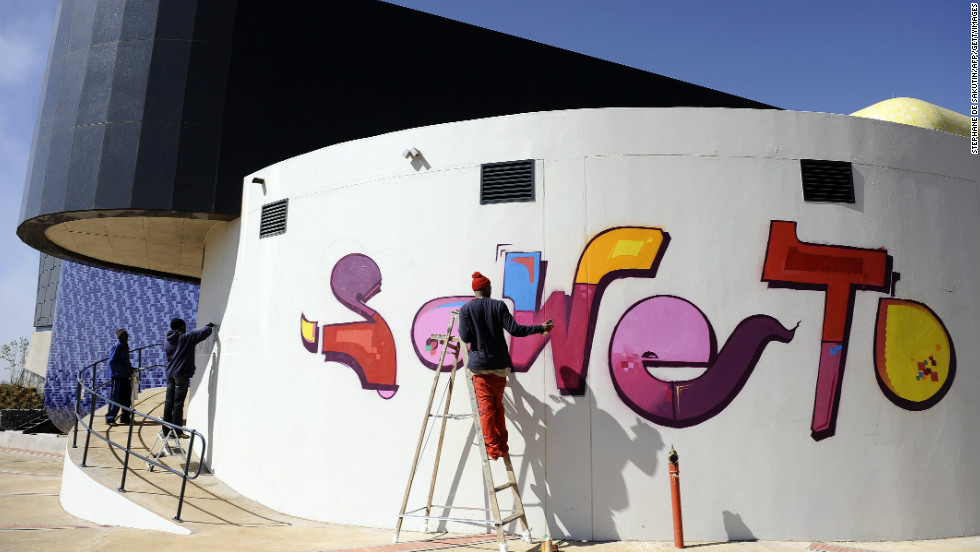 Laborers finish the paintwork on the newly inaugurated Soweto Theater, a powerful symbol of the Johannesburg's rebirth.