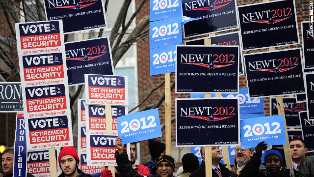Supporters of Republican presidential hopefuls and President Barack Obama hold placards outside a polling station in New Hampshire--11 months before the election.