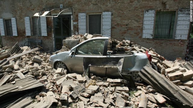 A car sits crushed by falling rubble from a building following an earthquake in Cavezzo, Italy on May 29, 2012.