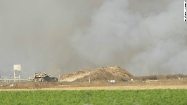 Smoke billows from the Gaza Strip as an Israeli army tank monitors the area on the southern Israel-Gaza border Friday.