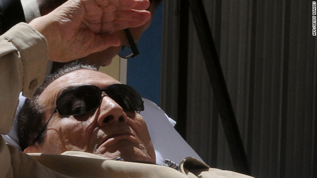 Ousted Egyptian president Hosni Mubarak gestures as he is wheeled out of a courtroom following his verdict hearing in Cairo on June 2, 2012. A judge sentenced Mubarak to life in prison after convicting him of involvement in the murder of protesters during the uprising that ousted him last year. AFP PHOTO/STRSTR/AFP/GettyImages