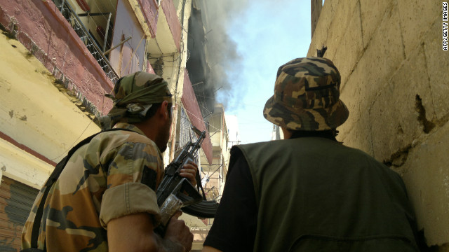 Armed militiamen look at smoke billowing in Tripoli's Sunni Muslim neighborhood of Bab al-Tabbaneh on Saturday.