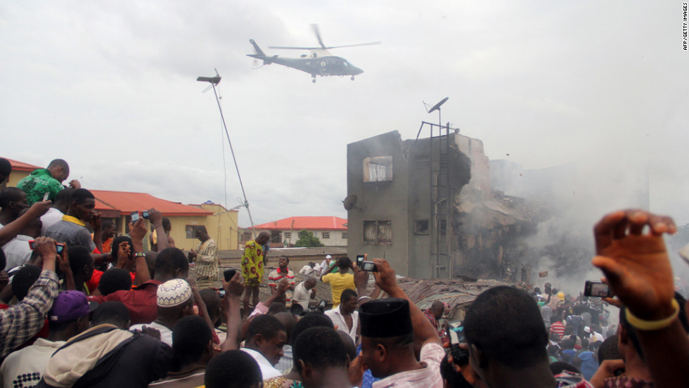 A helicopter hovers over the neighborhood in Lagos. Throngs of people flocked to the area despite debris, fires and thick smoke.