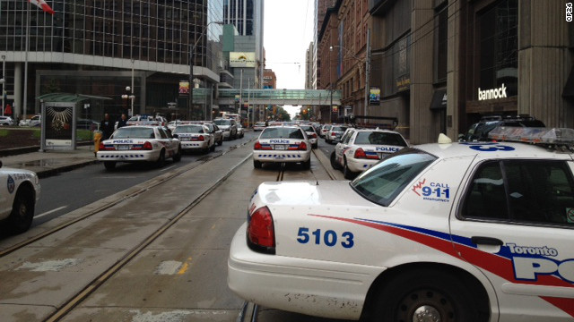 Police, firefighters and paramedics gather at Toronto's Eaton Centre shopping mall after reports of a shooting.