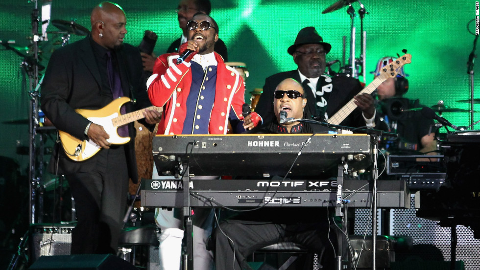 Singers Will.i.am and Stevie Wonder perform on stage. Wonder altered the lyrics to some of his songs to pay tribute to the queen.