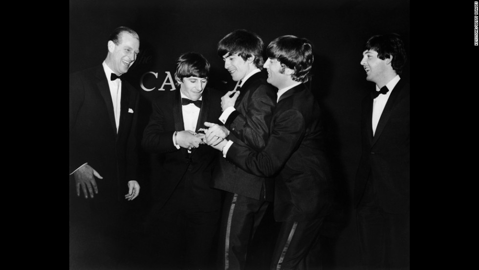 March 24, 1964: Prince Philip laughs as the Beatles fight over the single award that he presented to them at the Carl-Alan Awards ceremony.