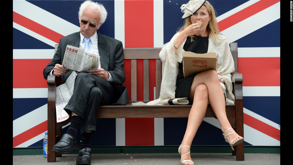 Two racegoiers sit in front of a Union Jack during Derby Day.