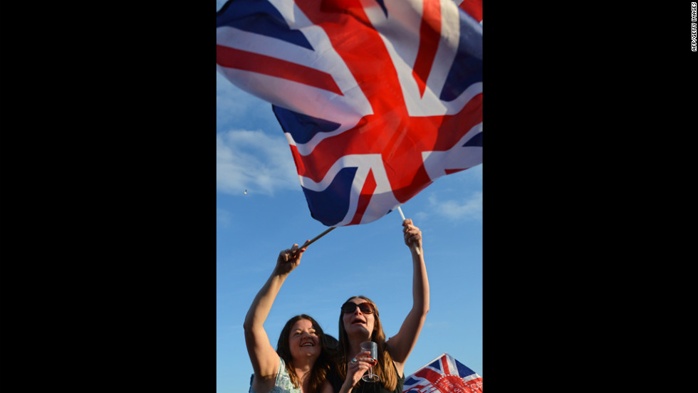 Spectators wave Britain's Union flag in London's Hyde Park as they watch the Diamond Jubilee Concert.